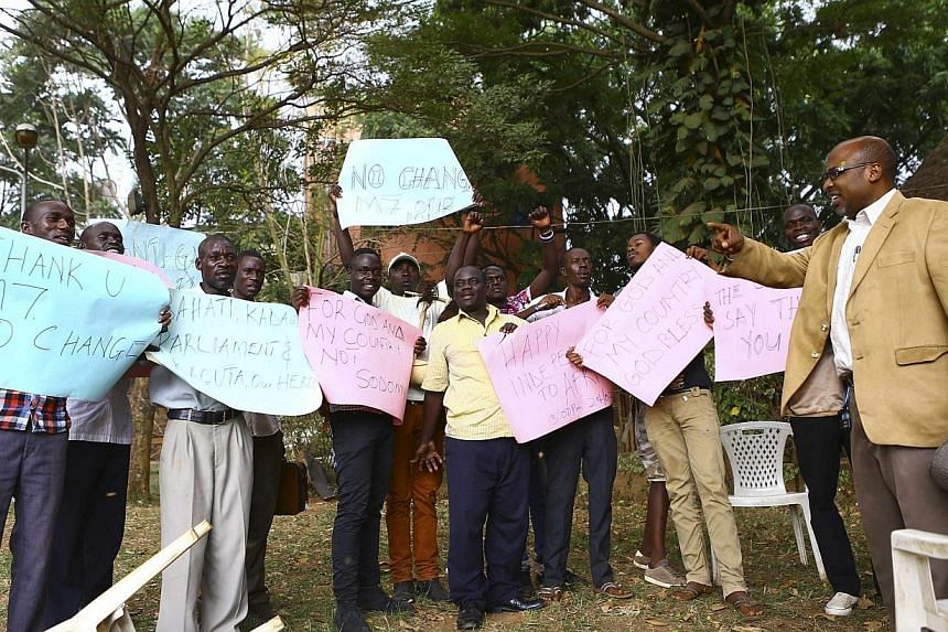 Ugandan anti-gay activist Pastor Martin Ssempa (right) leads anti-gay supporters as they celebrate after Uganda's President Yoweri Museveni signed a law imposing harsh penalties for homosexuality in Kampala, Feb 24, 2014.A Ugandan newspaper lis