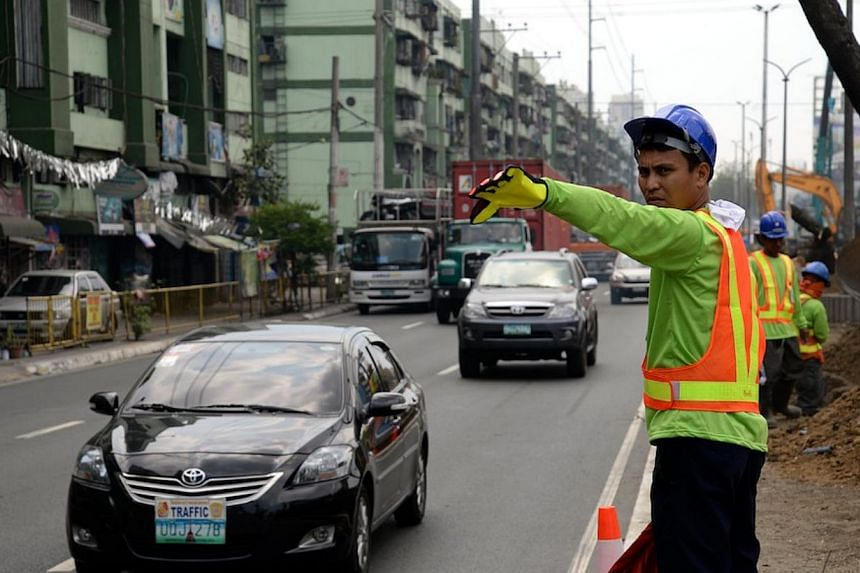 """Traffic aides direct motorists at a site where construction work on a new stage of an elevated highway known as the """"Skyway"""" began, on Feb 17, 2014. The """"Skyway"""" will link up with two other highways to provide motorists a fast, albeit expensive, to w"""