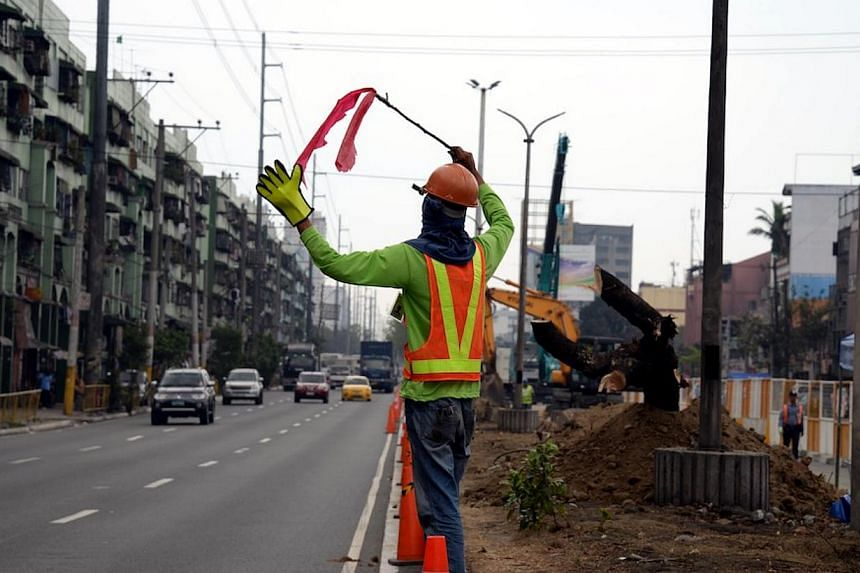 "Traffic aides direct motorists at a site where construction work on a new stage of an elevated highway known as the ""Skyway"" began, on Feb 17, 2014. The ""Skyway"" will link up with two other highways to provide motorists a fast, albeit expensive, to w"