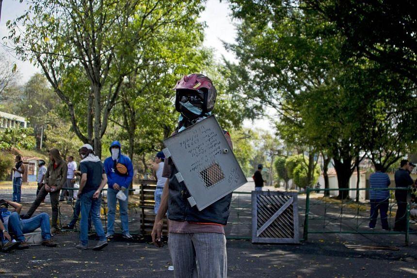 Venezuelan demonstrators protesting against the government of President Nicolas Maduro in San Cristobal, capital of the western border state of Tachira, Venezuela, on Feb 24, 2014. -- PHOTO: AFP