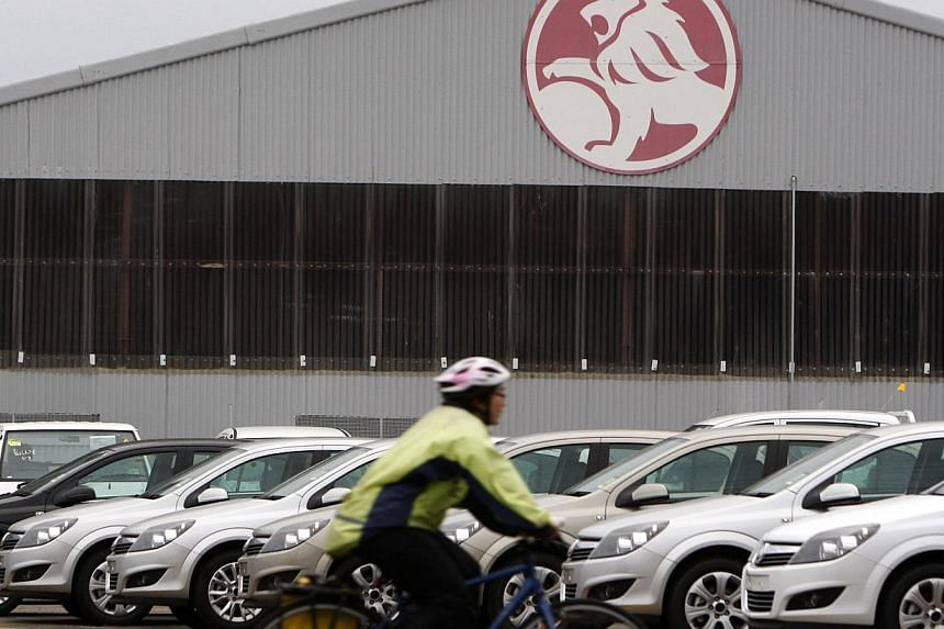 A cyclist rides past a General Motors Holden storage facility in Melbourne on June 2, 2009. General Motors on Tuesday significantly expanded the recall of vehicles found to have an ignition defect that can cause them to suddenly turn off, a problem l