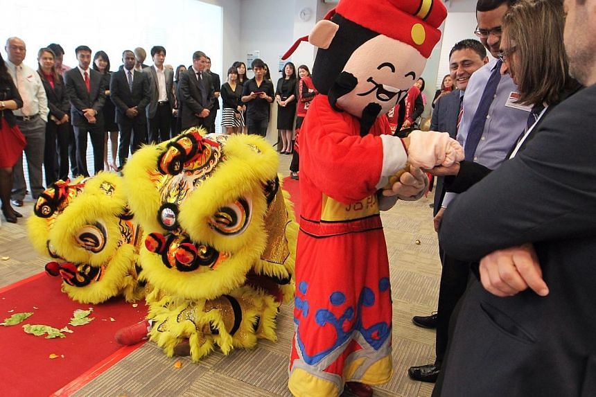 A God of Fortune and a lion dance troupe mingle with guests at the official opening of LSBF's new Singapore campus at the Springleaf Tower on Feb 26, 2014.-- ST PHOTO: NEO XIAOBIN