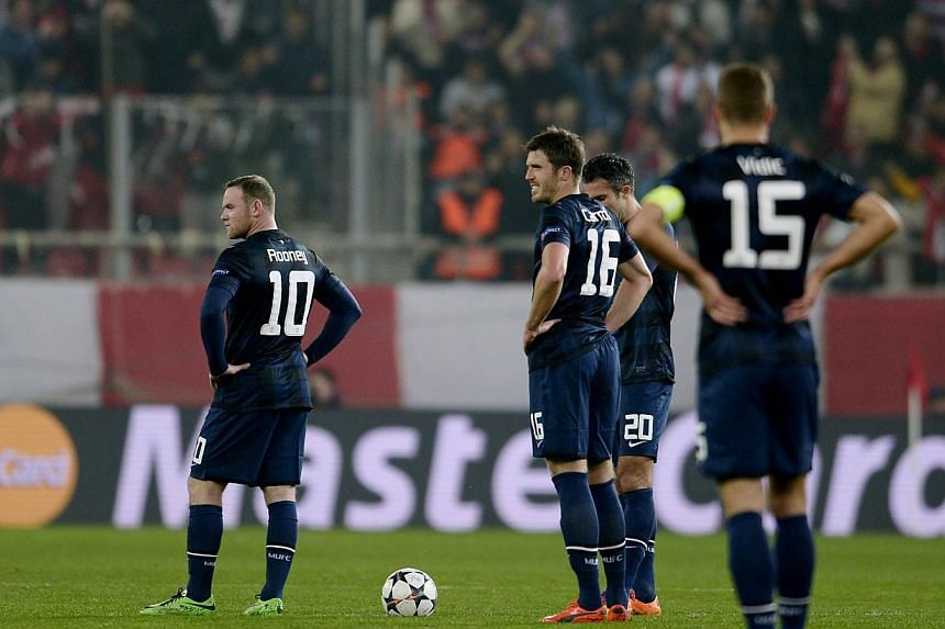 (From left) Manchester United's British forward Wayne Rooney, British midfielder Michael Carrick, Dutch forward Robin van Persie and Serbian defender Nemanja Vidic in disbelief after Olympiakos scored a second goal during the round of 16 Champions Le