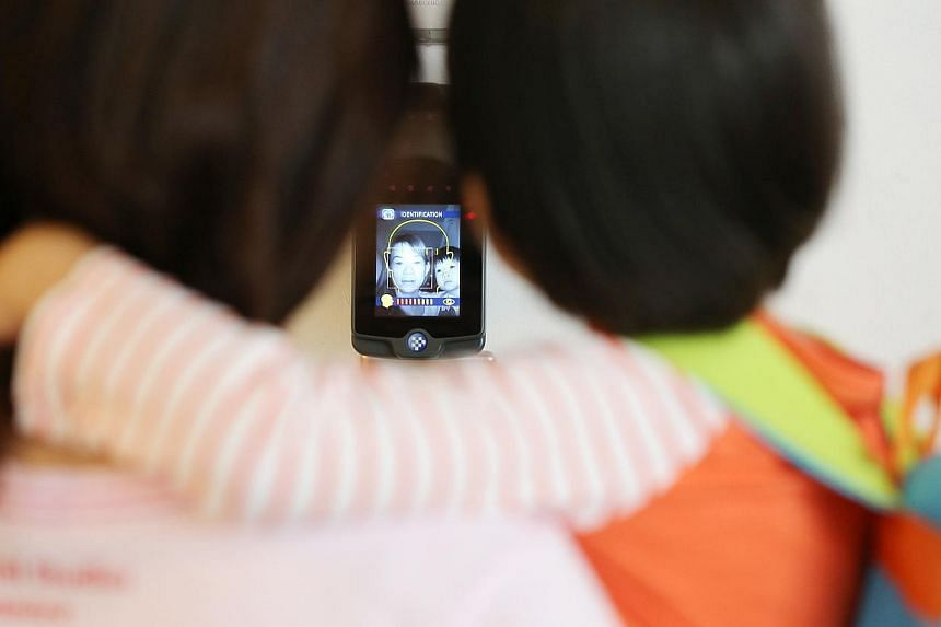 Parent Adeline Low, 38, with her three-year-old daughter Natalie, getting her face scanned at Pat's Schoolhouse in Sembawang Country Club. The facial recognition system matches guardians' faces to images saved in a database, and the front door is unl