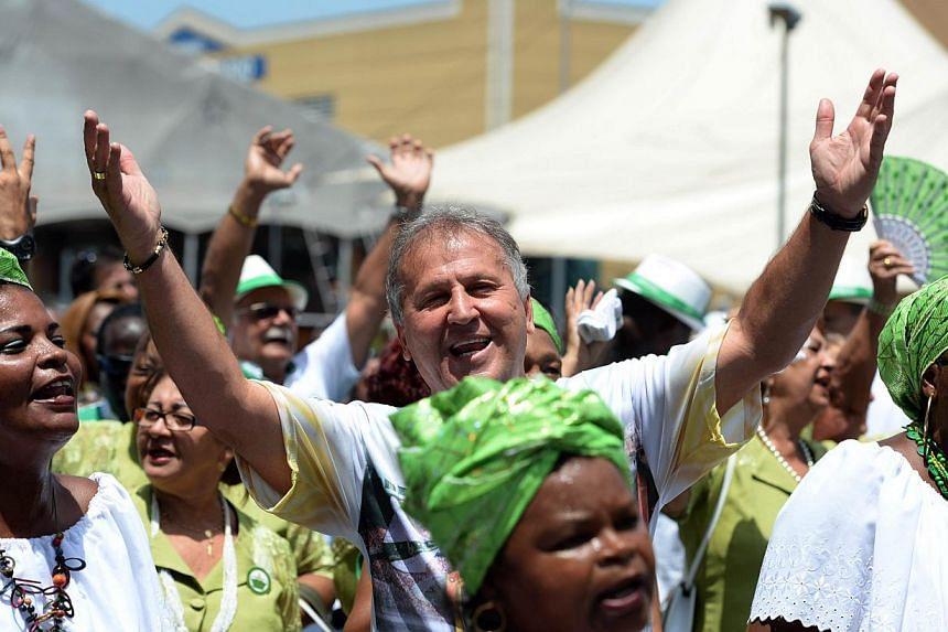 "Former Brazilian football star, Arthur Antunes Coimbra, aka ""Zico"" (centre) dances with members of the Imperatriz Leopoldinense samba school at Samba City in Rio de Janeiro, Brazil, on Febuary 13, 2014. -- FILE PHOTO: AFP"