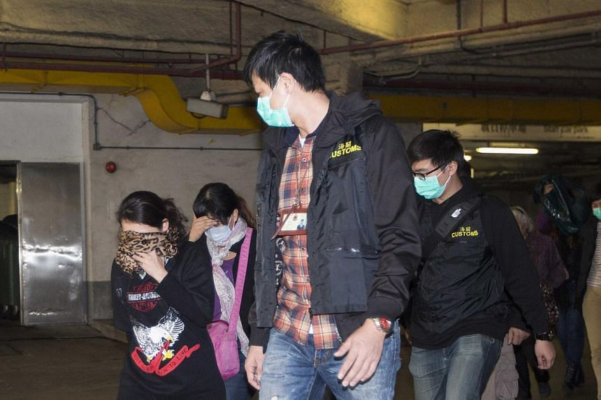 """In this file picture of January 3, 2014, Hong Kong Customs officers detain mainlanders who had tried to carry excessive amount of infant formula out of the city, defying the limit of """"two tins"""" per person. Mainlanders have come in droves to smuggle i"""