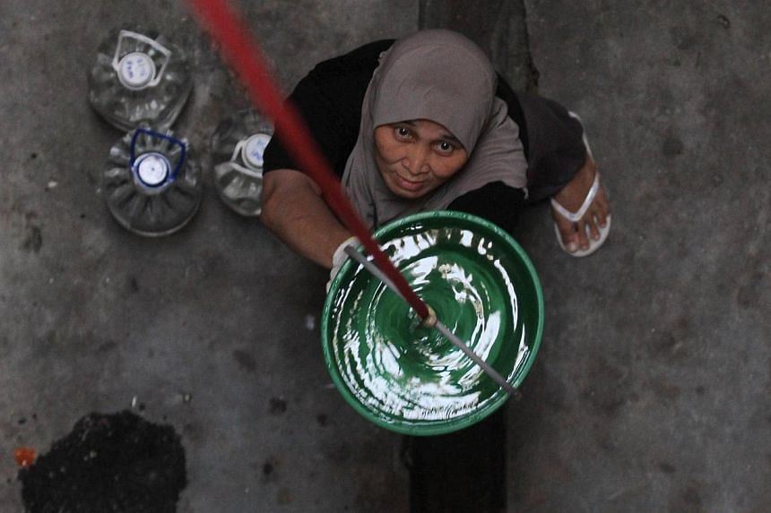 Resident of Taman Setia Balakong, Noraini Baini, was helping her neighbour who standby at fourth floor and pulling all the water that they have filled into the bucket and bottles. Malaysia's government signed a pact on Wednesday, Feb 26, 2014, w