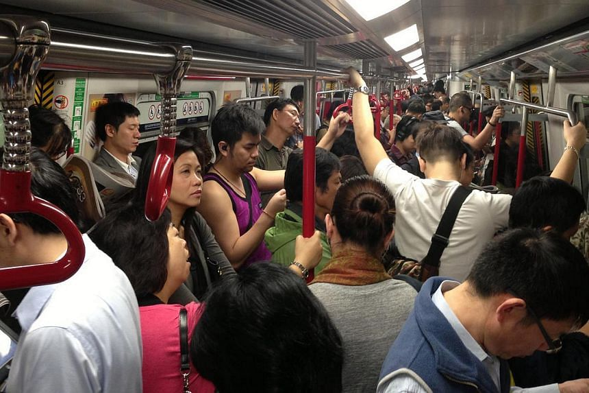 Commuters inside an MTR train during the morning peak hour in Hong Kong. Hong Kong is pondering whether to rip out some seats from overcrowded metro trains to give the city's smartphone-addicted population more room to interact with their devices.&nb