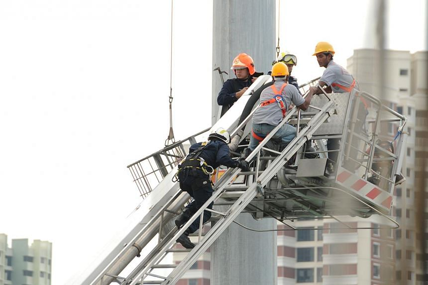 The two men secured with harness and carabiner escorted by SCDF to safety.-- PHOTO: SINGAPORE CIVIL DEFENCE FORCE