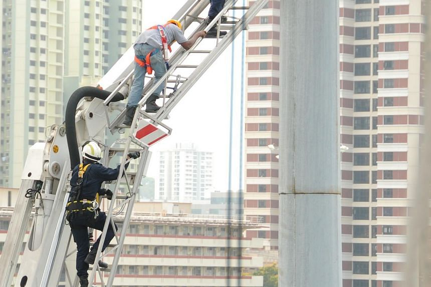 The two men secured with harness and carabiner escorted by SCDF to safety. -- PHOTO: SINGAPORE CIVIL DEFENCE FORCE