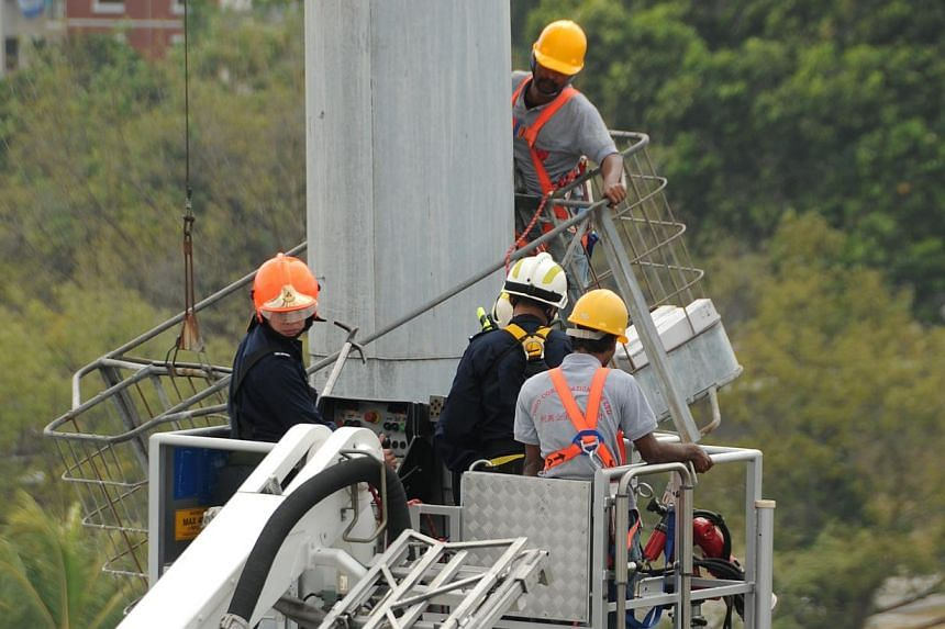The two men secured with harness and safety lines being brought to safety onto the rescue platform of the aerial appliance.-- PHOTO: SINGAPORE CIVIL DEFENCE FORCE