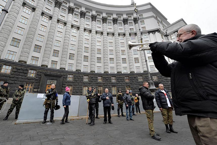 A musician plays the Ukrainian national anthem for Maidan activists guarding the ministers' cabinet in Kiev, on Feb 22, 2014. The makeup of Ukraine's new government will be announced on Wednesday, Feb 26, 2014, on Kiev's Independence Square, the scen
