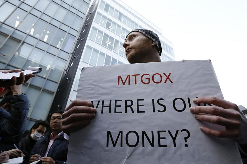 Kolin Burges, a self-styled cryptocurrency trader and former software engineer from London, holds a placard to protest against Mt. Gox, in front of the building where the digital marketplace operator was formerly housed in Tokyo on Feb 26, 2014.