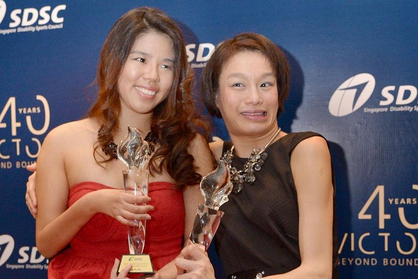 President Tony Tan presented the Outstanding Athlete Award to Laurentia Tan (right) and Yip Pin Xiu at the Singapore Disability Sports Council 40th anniversary charity dinner and sports award night 2014 at the Stamford Ballroom, Raffles City Conventi