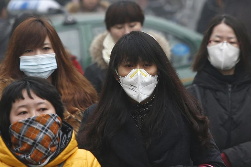 Commuters wearing masks make their way amid thick haze in the morning in Beijing, Wednesday, Feb 26, 2014.China's biggest online face-mask sellers were running out of stock on Wednesday as consumers rushed to protect themselves from smog that h