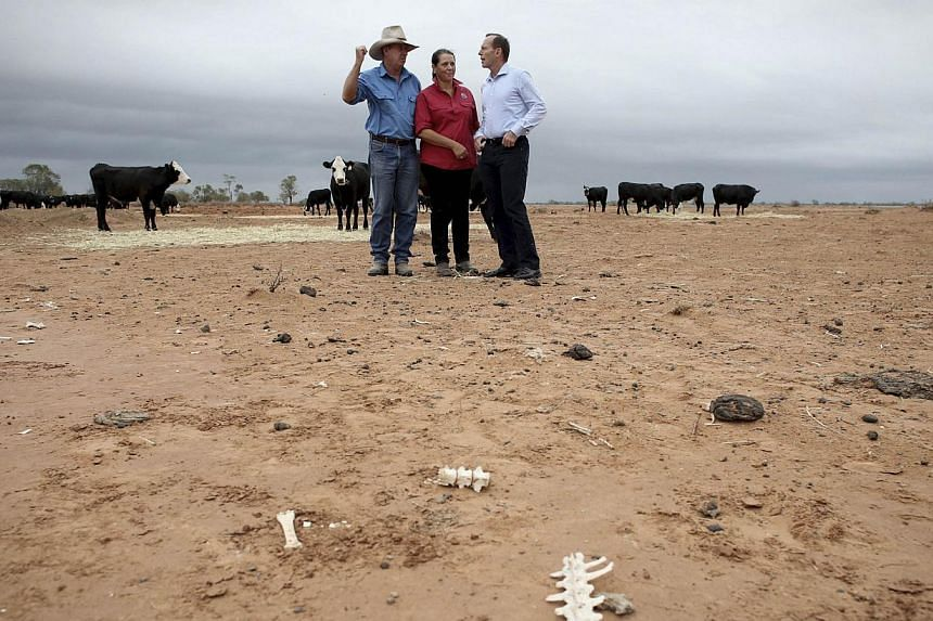 """Australian Prime Minister Tony Abbott (right) meets with outback graziers Phillip and Di Ridge of their property named """"Jandra"""" near Bourke in western New South Wales, on Feb 16, 2014. -- FILE PHOTO: REUTERS"""