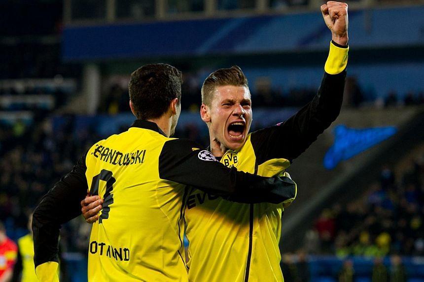 Borussia Dortmund's Lukasz Piszczek (right) and Robert Lewandowski celebraing after scoring a goal against Zenit Saint Petersburg during their Uefa Champions League Champions League last 16, first-leg football match at Petrovsky Stadium in Russia's s