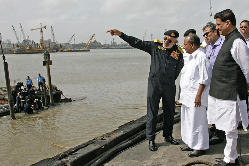 In this handout photograph released by the Ministry of Defence,Chief for Indian Naval Staff Admiral D.K. Joshi (left) briefs Indian Defence Minister A.K. Antony (centre) at the scene as Indian Navy personnel work at the conning tower of the str