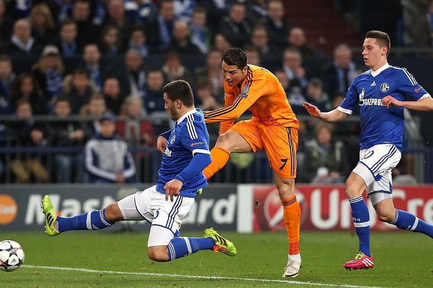 (From left) Schalke's defender Sead Kolasinac, Real Madrid's Portuguese forward Cristiano Ronaldo and Schalke's midfielder Julian Draxler vie for the ball during the first-leg round of 16 Champions League football match in Gelsenkirchen, western Germ