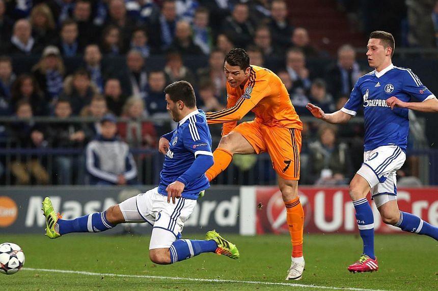 (From left) Schalke's defender Sead Kolasinac, Real Madrid's Portuguese forward Cristiano Ronaldo and Schalke's midfielder Julian Draxler vie for the ball during the first-leg round of 16 Champions League football match in Gelsenkirchen, western Germ