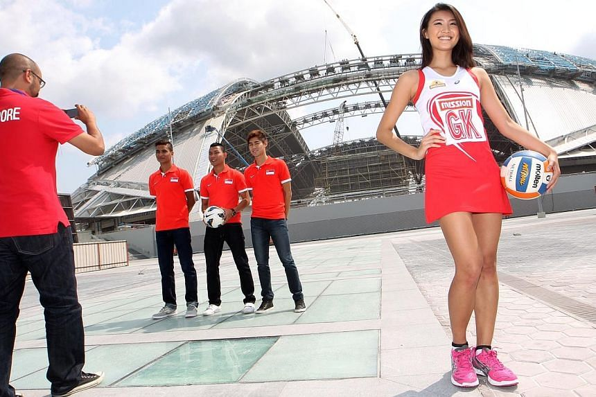 Singapore national netball player Cheryl Ann Lee (extreme right) and the national footballers (from left) Safuwan Baharudin, Isa Halim, and Gabriel Quak line up for photo opportunities in front of the Singapore Sports Hub that is currently undergoing