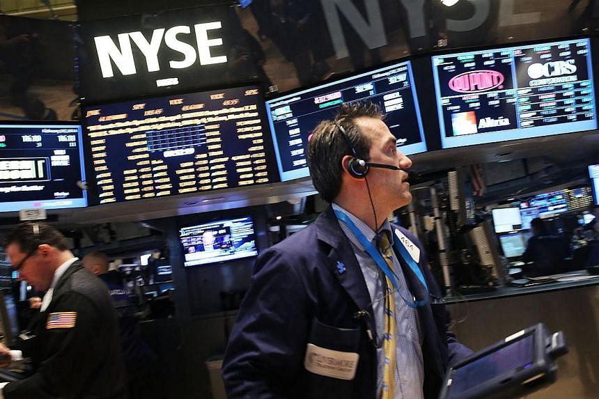 Traders work on the floor of the New York Stock Exchange on Feb 20, 2014. United States stocks were nearly flat on Feb 26, with the S&P 500 holding below resistance levels even as retailers gained for a second day. -- FILE PHOTO: AFP