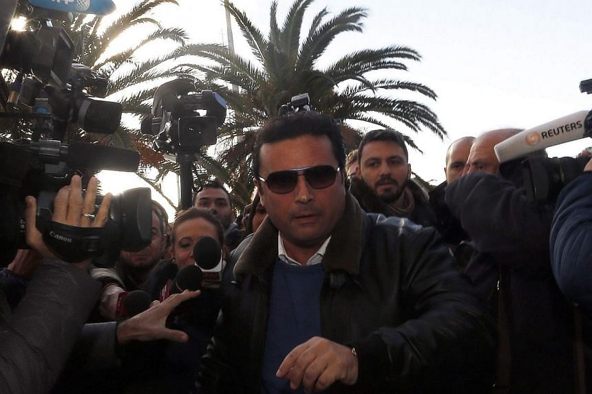 Captain Francesco Schettino (centre) arrives at the Giglio harbour Feb 27, 2014.Italian captain Francesco Schettino on Thursday returned on board his stricken Costa Concordia cruise ship, more than two years after leaving it in a hurry as it sa