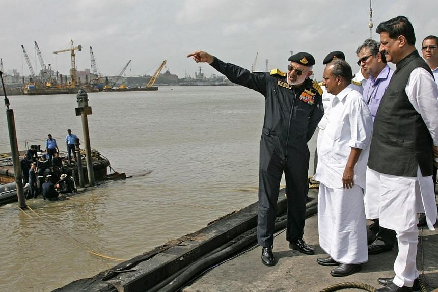 In this handout photograph released by the Ministry of Defence on Aug 14, 2013, Chief for Indian Naval Staff, Admiral D.K. Joshi (left) briefs Indian Defence Minister A.K. Antony (centre) at the scene as Indian Navy personnel work at the conning towe
