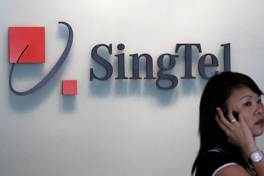 A woman speaks on a mobile phone in front of a SingTel logo at the company's headquarters in Singapore. Amid online furore based on the belief that SingTel would be charging customers for using Internet services such as Whatsapp and Skype, the telco
