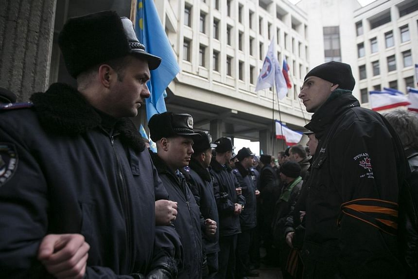 Ukrainian police separate ethnic Russians (right) and Crimean Tatars during rallies near the Crimean parliament building in Simferopol Feb 26, 2014. Armed men have seized the regional government headquarters and parliament on Ukraine's Crimea peninsu