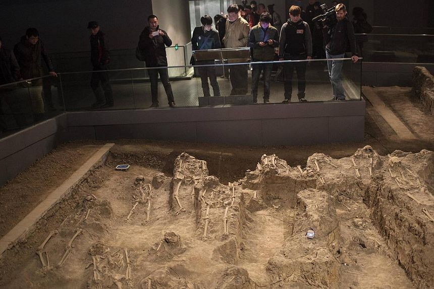 Journalists and visitors look at skeletons of victims of the 1937 Nanjing massacre at the Nanjing Massacre Museum during a media trip, in Nanjing, Jiangsu province, Feb 19, 2014. Chinese lawmakers approved on Thursday, Feb 27, 2014, national rem