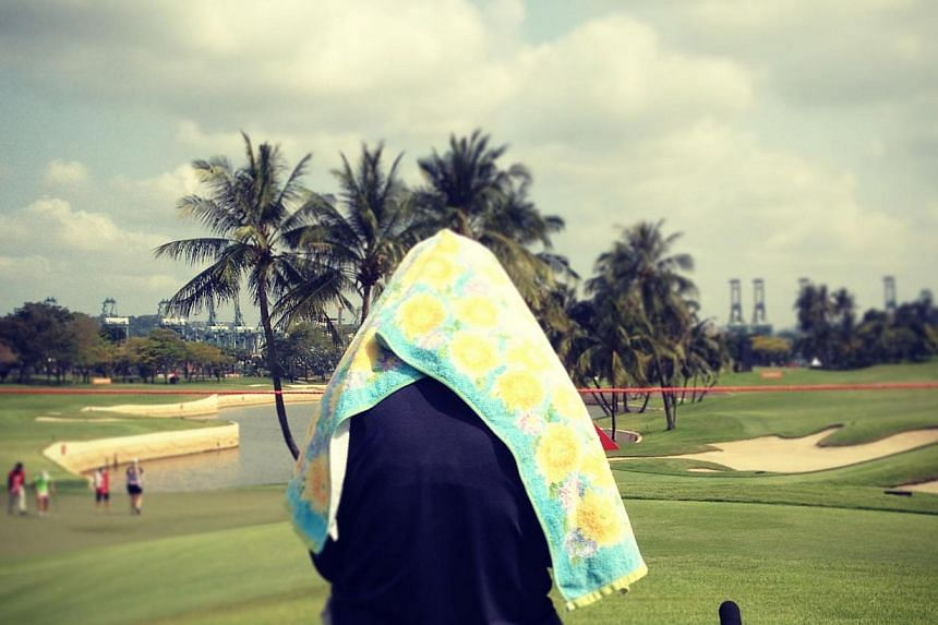 A spectator shelters himself from the heat during the opening round of the HSBC Women's Champions golf at Sentosa Golf Club. -- PHOTO: KHUA CHEE SIONG