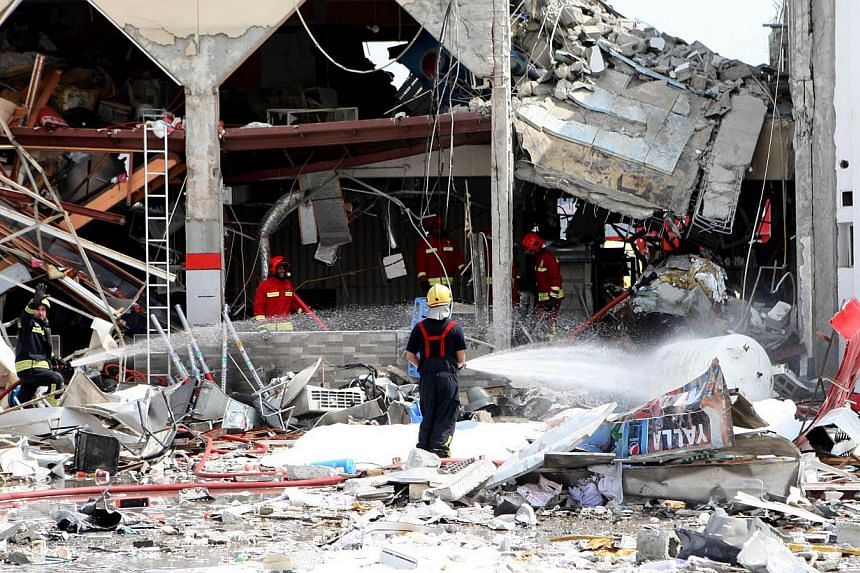 """Firefighters spray the site of a blast in Doha with water as Qatari state television said """"gas cylinder"""" explosion in the Gulf emirate's capital Doha killed and wounded several people, on Feb 27, 2014. Twelve people were killed, including two childre"""