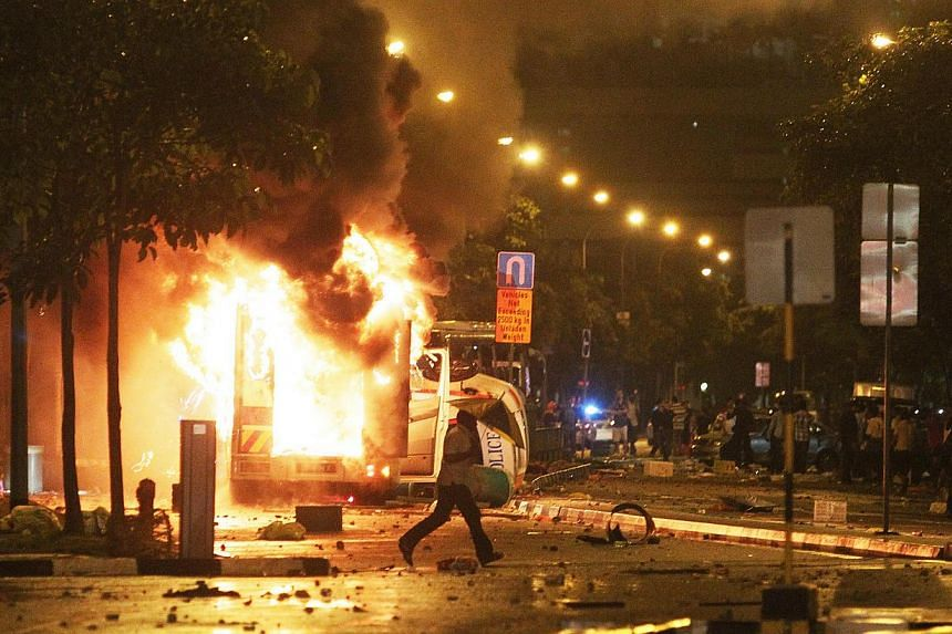 A man with an umbrella runs in front of a burning ambulance during a riot, involving almost 400 people, which broke out in Little India along Race Course Road, on Dec 8, 2013. The traffic police officer who led a group of seven others to evacuate an