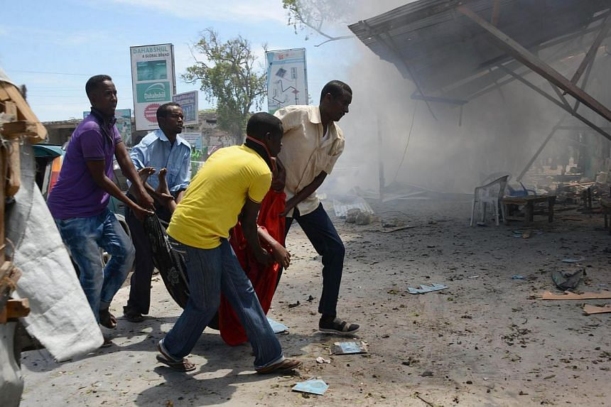 People carry a wounded individual after a car bomb exploded in the Somali capital Mogadishu, on Feb 27, 2014. At least 10 people were killed in an explosion when a suicide bomber drove his car into a tea shop near the national security headquarters i