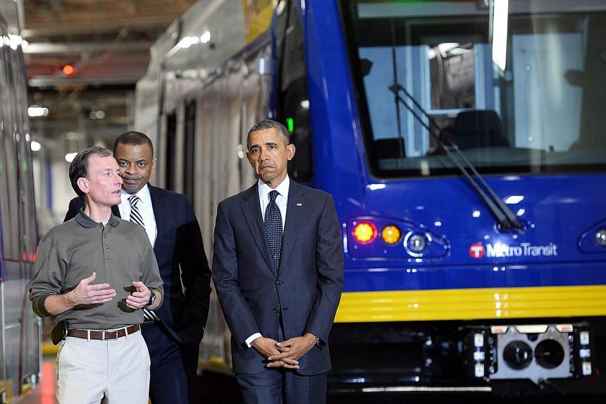 US President Barack Obama (centre) and Secretary of Transportaion Anthony Foxx (right) tour the Metro Transit Light Rail Operations and Maintenance Facility in St Paul, Minnesota, on Feb 26, 2014. President Barack Obama on Wednesday unveiled a four y