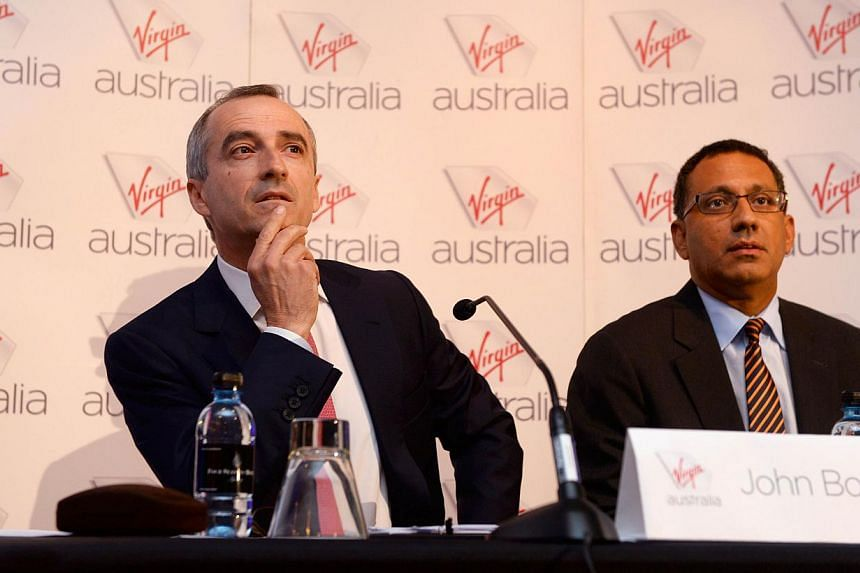 Virgin Australia chief executive John Borghetti (left) and chief financial officer Sankar Narayan (right) speak during a press conference in Sydney on Feb 28, 2014. -- PHOTO: AFP