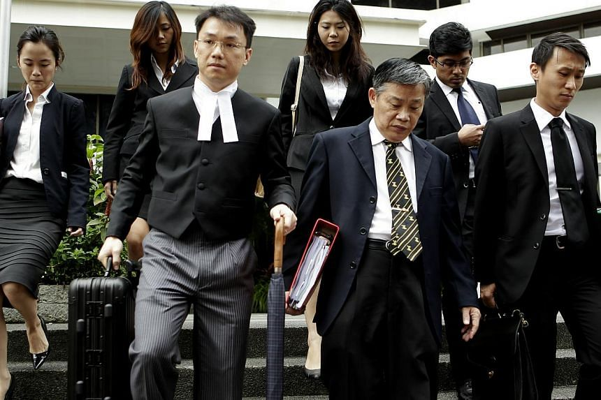 Tey Tsun Hang (left, holding an umbrella and a suitcase) leaving the court, after the sex-for-grades trial. -- ST FILE PHOTO: WONG KWAI CHOW