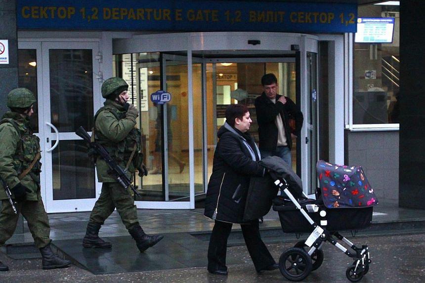 Armed men patrol at the airport in Simferopol, Crimea, Feb 28, 2014. -- PHOTO: REUTERS