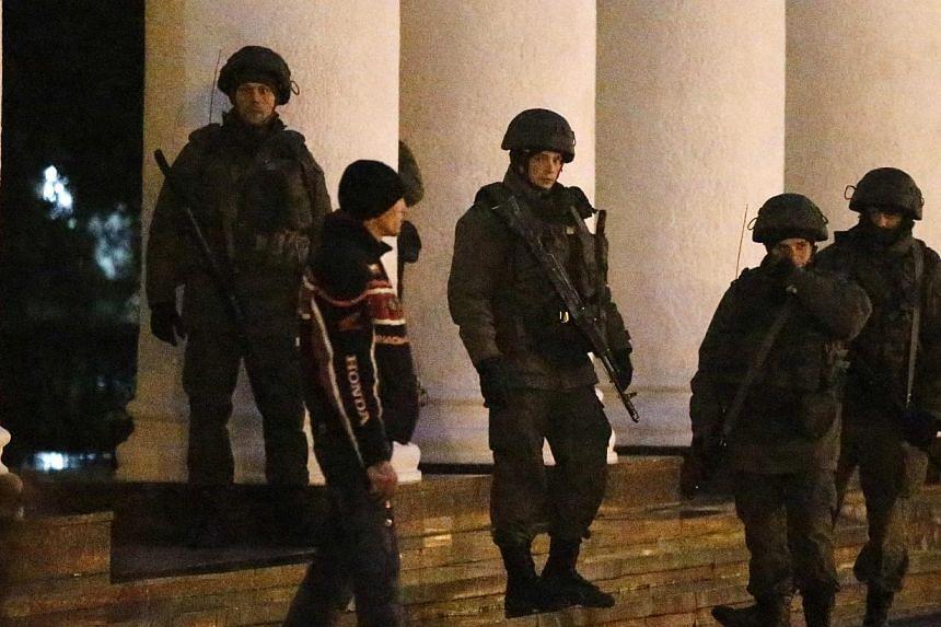 Armed men stand guard at the airport in Simferopol, Crimea, Feb 28, 2014. -- PHOTO: REUTERS