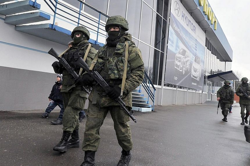Unidentified armed men patrol outside of the Simferopol airport on Feb 28, 2014. Ukraine's security authorities said on Friday, Feb 28, 2014, they had regained control of two airports on the volatile Crimean peninsula that had been seized by gunmen t