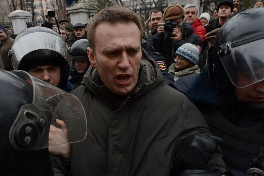 Police officers detain protest leader Alexei Navalny outside Zamoskvoretsky district court in Moscow, on Feb 24, 2014, during a protest against the trial of eight people accused of instigating mass riots after an opposition rally on Moscow's on Bolot