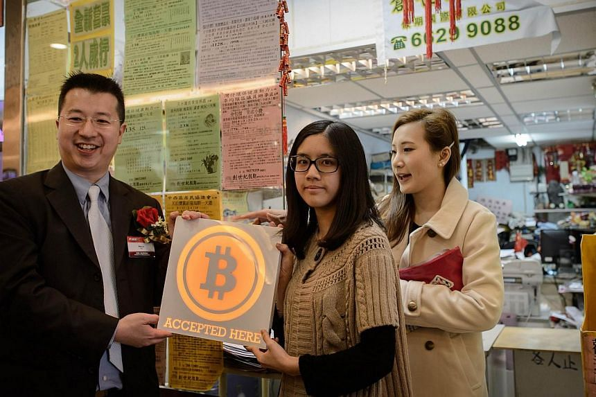 ANXBTC bitcoin exchange Chief Executive Ken Lo (left) poses with a shopkeeper accepting bitcoins during the opening ceremony of the city's first bitcoin retail shop in Hong Kong, on Feb 28, 2014. -- PHOTO: AFP