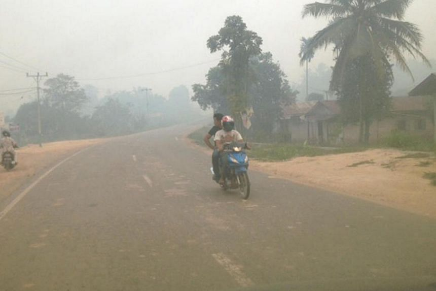 A motorcyclist and his rider braving the haze in Dumai in Indonesia's Riau province on July 22, 2013. Clearer international rules on pollution that crosses national borders are needed and states should join forces to enforce and comply with polluti