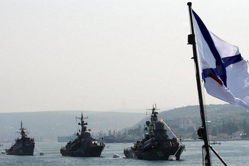 Russian Black Sea Navy ships being anchored in Sevastopol bay with a Russian naval flag (right) flying, on July 28, 2011. Russia's Black Sea fleet denied its forces were involved on Friday, Feb 28, 2014, in seizing or blockading the Belbek military a