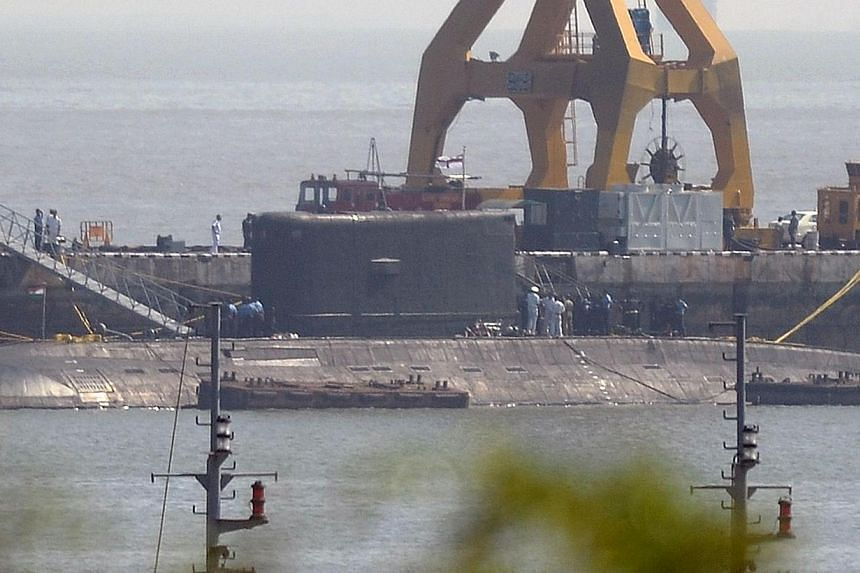 An Indian Navy submarine, believed to be the Russian-built INS Sindhuratna, is seen anchored at the naval dockyard as a fire truck (partially obscured) and support crew are pictured in the background in Mumbai, on Feb 27, 2014. Malfunctioning and age