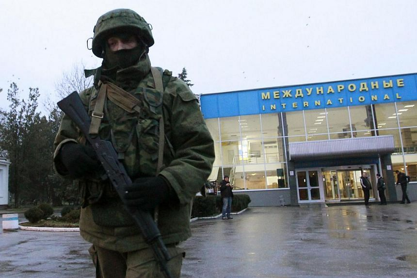 """An armed man patrols at the airport in Simferopol, Crimea, on Feb 28, 2014.Ukraine's interior minister on Friday accused Russian forces of staging an """"armed invasion"""" in Crimea, claiming they had blocked one military air base and entered an air"""