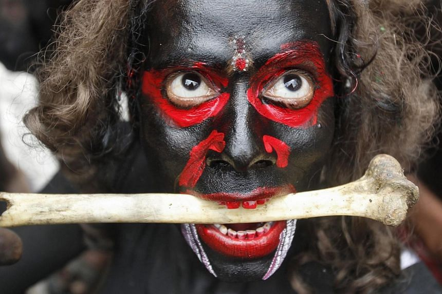 A man dressed as a demon performs with a bone during a religious procession at the Mahashivratri festival in the northern Indian city of Allahabad on Feb 27, 2014. -- PHOTO: REUTERS