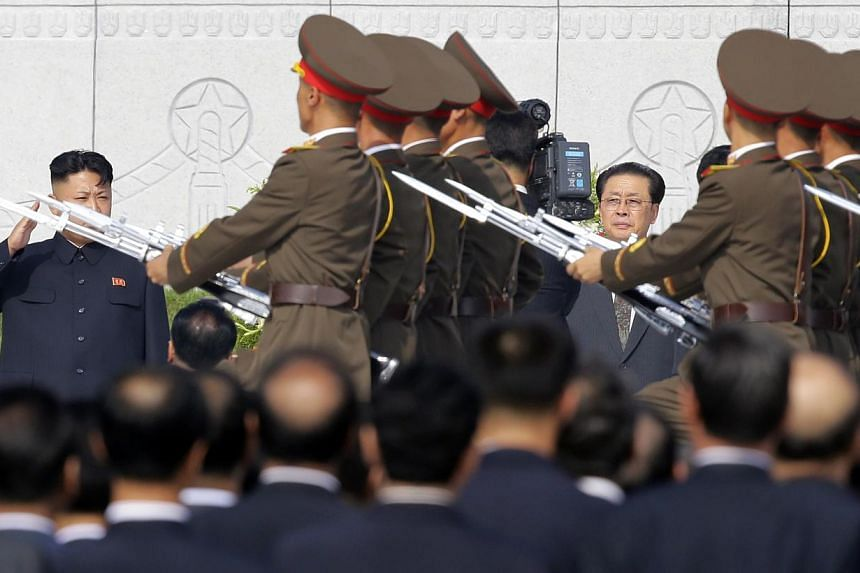 North Korean leader Kim Jong Un (left) salutes to members of the honour guards as he attends a commemoration event at the Cemetery of Fallen Fighters of the Korean People's Army (KPA) in Pyongyang. -- PHOTO: REUTERS