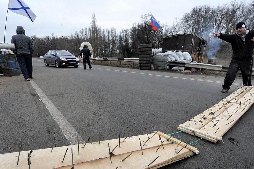 Members of a local militia use makeshift road spike barriers to block a highway that connects the Black Sea Crimea peninsula to mainland Ukraine at their checkpoint near the city of Armyansk, on Feb 28, 2014.The newly-chosen prime minister of t